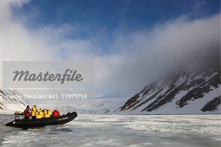 Pneumatique Zodiac avec des touristes exploration arctique du paysage au soleil de l'été, du Nord au Spitzberg, Svalbard, en Norvège, Scandinavie, Europe