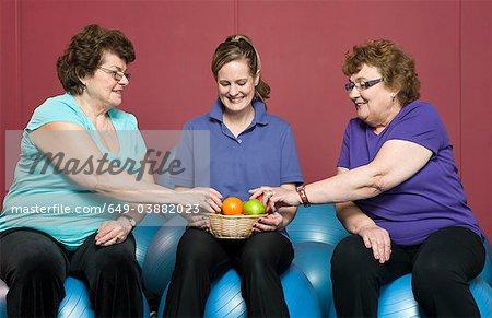 Older woman having fruit in gym