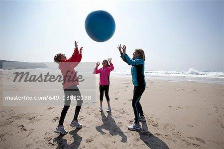 Famille jouant avec une balle sur la plage