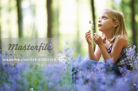 Fille assise dans le champ de fleurs