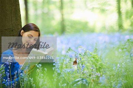 Femme lisant dans le champ de fleurs
