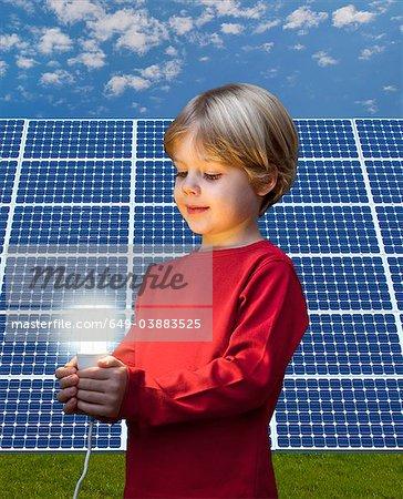 Boy with light bulb by solar panel