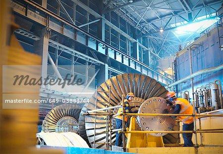 Travailleurs inspectent la turbine dans une centrale électrique