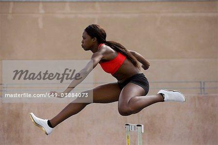 Runner jumping over hurdles on track