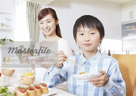 Mère et fils, manger des sushis chirashi