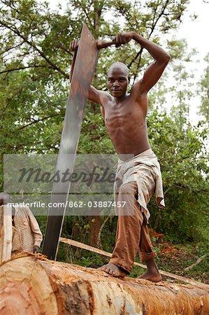 Burundi. Un homme coupe un arbre en planches dans une fosse de sciage traditionnel.