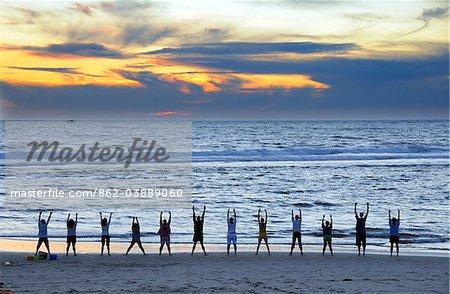 Un groupe de personnes faire exercer face à l'océan Atlantique, au crépuscule. Costa Nova, Beira Litoral, Portugal