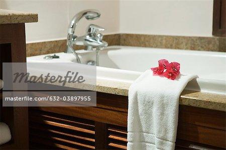 Frisches Handtuch, verziert mit Blume Köpfe hängen am Rand der Badewanne