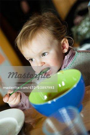 Kleinkind Mädchen selbst mit Löffel füttern