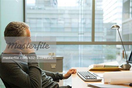 Mann sitzt am Schreibtisch im Büro, in Gedanken Wegsehen