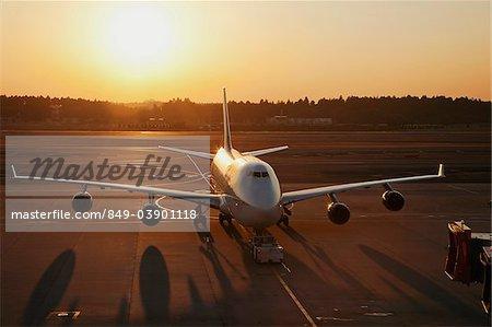 Avion sur le tarmac, soleil derrière. L'aéroport de Narita, Japon