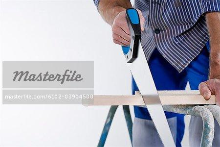 Un menuisier à l'aide d'une scie.