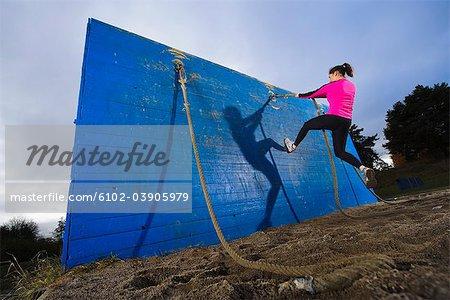 Femme avec corde, parcours d'obstacles de mur d'escalade