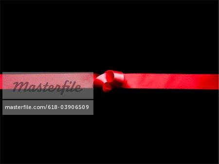 Ruban rouge avec noeud sur un fond noir.