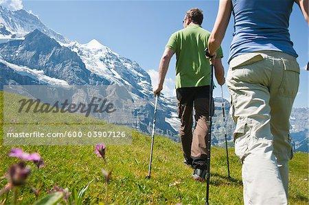 Illnesses paar von Wandern über Walking-Stöcke, Berner Oberland, Schweiz