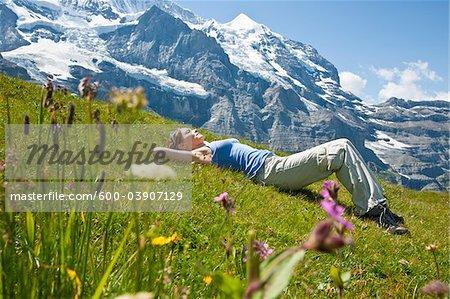 Woman Lying on Grass on Mountain Side, Bernese Oberland, Switzerland