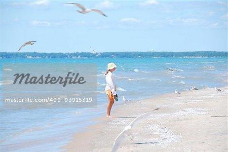 Young girl on a beach among flying seagulls