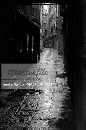 Dark alley in the rainy streets of Venice, Italy.
