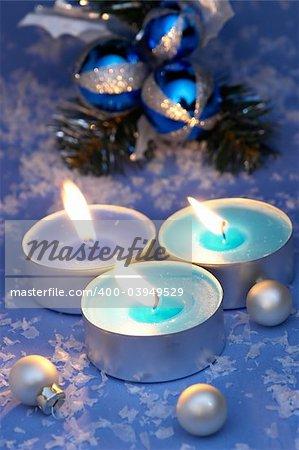 Burning candles, ornaments, blue setting