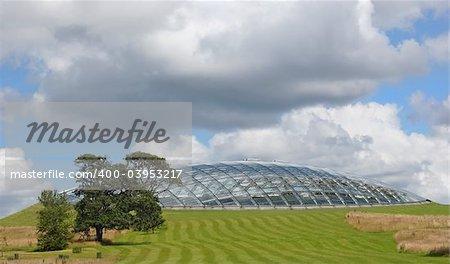 Futuristic eco dome made of glass panels set into a grass hillside.