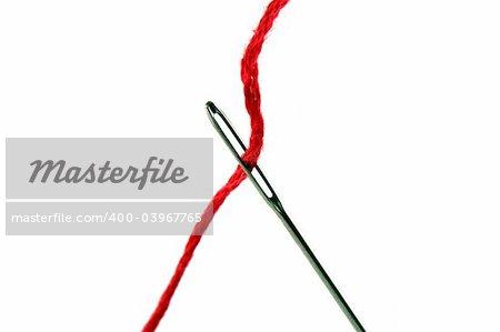Une aiguille et le fil rouge sur blanc