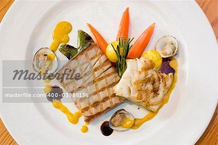Gegrilltes Hähnchen-Steak mit Austern, Kartoffeln und Gemüse serviert. Mahlzeit beträufelt mit Senfsauce.