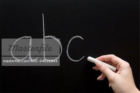 Female teacher writing on a chalkboard.