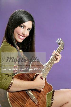 Belle brune jouant de la guitare acoustique sur fond violet