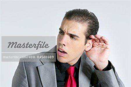 Homme d'affaires main dans l'oreille en guise de signe de surdité