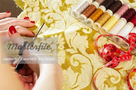 A hand of a dressmaker cutting a cloth