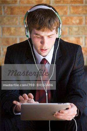 Unternehmer tragen Kopfhörer und Using iPad