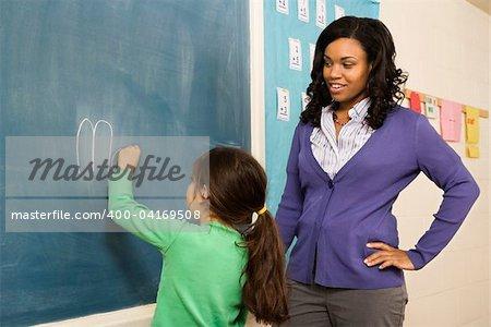 Teacher watching young female student write on blackboard. Horizontally framed shot.