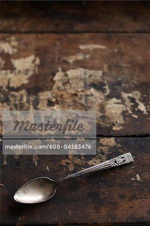 Besudelte silberner Löffel auf hölzernen Hintergrund