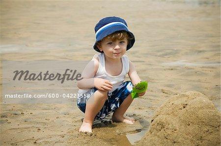 Porträt eines jungen spielen im Sand am Strand
