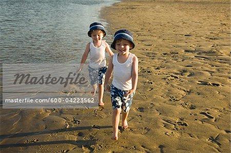 Zweibettzimmer mit jungen zu Fuß am Strand