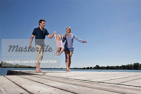 Parents se balançant la fille sur le quai