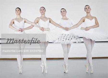 Ballet dancers holding hands in studio