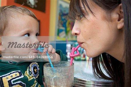 Fils de mère et le bébé à l'aide de pailles bouclés
