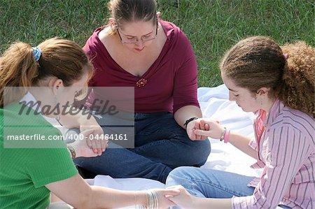 A group of teen girls having a prayer circle outdoors.