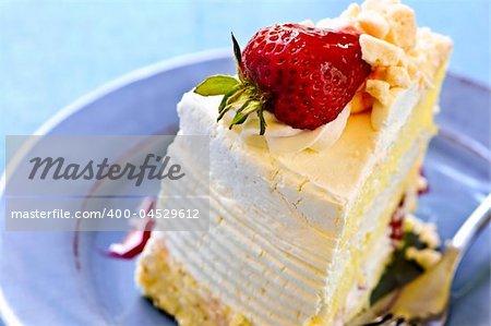 Part de gâteau fraise meringue sur une plaque