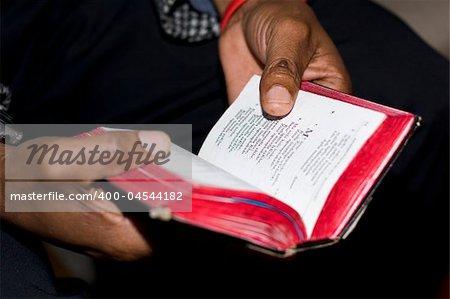 Deux mains tenant un vieux, un livre de prières à un service Église méthodiste dimanche sont le symbole de la foi du peuple sud-africain. Note : faible profondeur de champ se concentre sur seulement le pouce et le texte voisin.