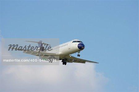 Aircraft landing against blue sky