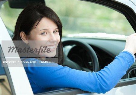 Portrait of a smiling brunette woman driving