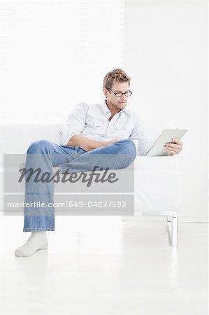 Mann mit Tablet auf couch