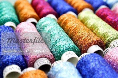Set of coloured bobbins of lurex thread