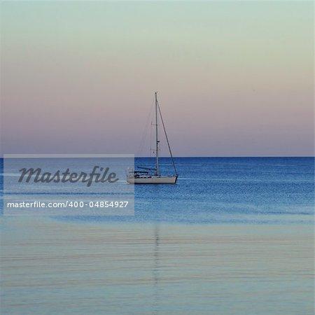 Sailboat reflected on sea water. Sunset sea and sky horizon.