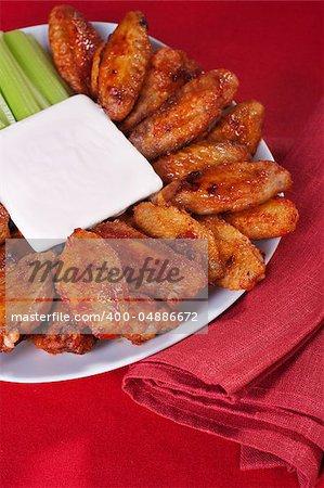 Büffel-Hähnchenflügel auf Teller mit Blue Cheese Sauce und Sellerie.
