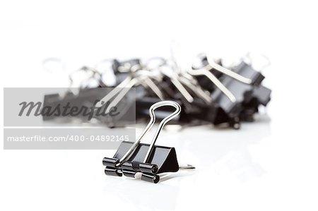 A black binder clip against a white background