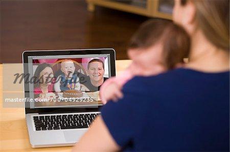 Frau mit Baby mit Video-Chat mit Freunden