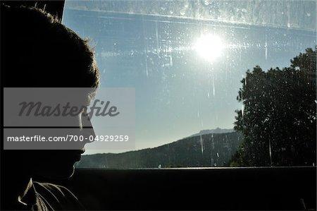 Garçon à la recherche des voitures hors fenêtre